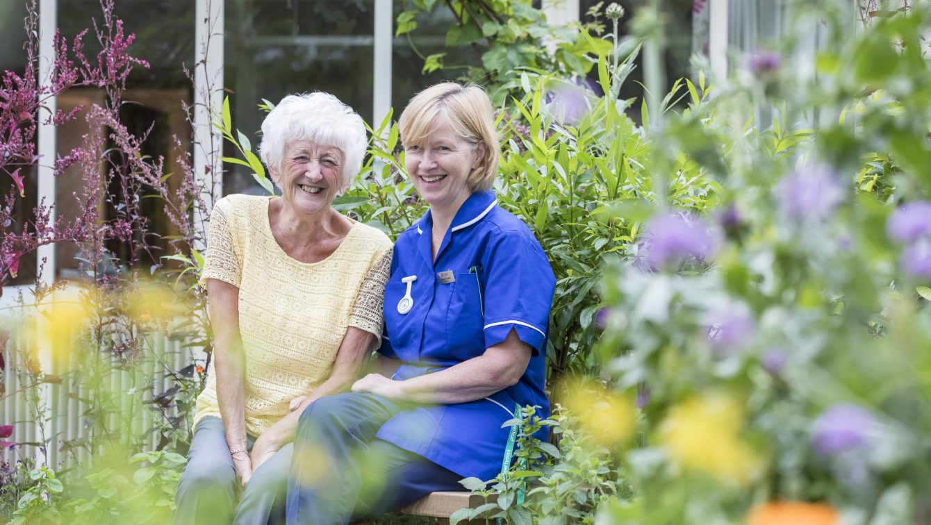 Nurse With Patient In Hospice Garden
